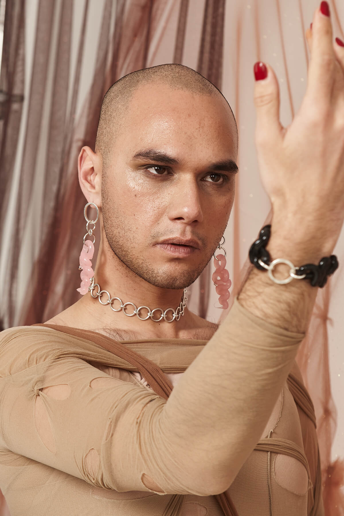 A model wearing pink silicone pendant earrings, a silver choker, and a black silicone bracelet.